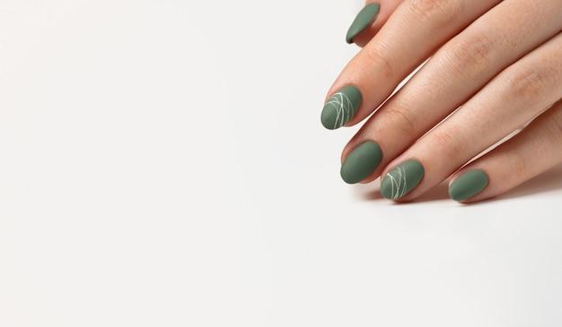 밝은 회색 배경에 녹색 올리브 무광택 손톱을 가진 젊은 여성의 손. 매니큐어, 페디큐어 미용실 개념입니다. 텍스트 또는 로고를 위한 공간을 복사합니다. 젤 광택 및 추상 흰색 거미줄 패턴입니다.