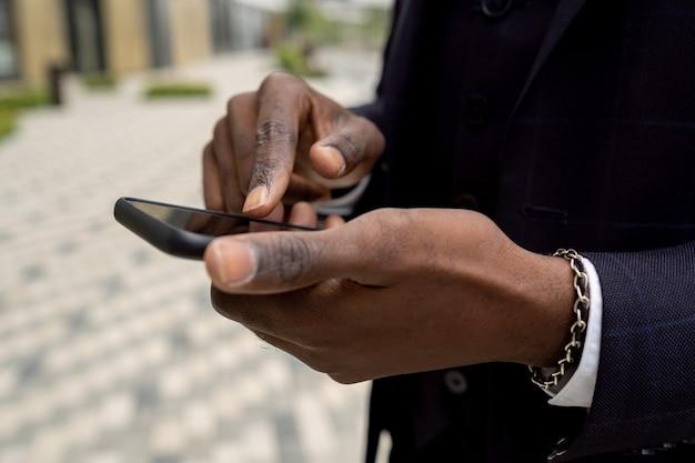 Руки африканского бизнесмена, указывая на экран смартфона