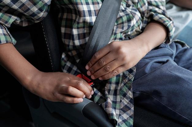 Руки африканского ребенка пристегивают ремень безопасности перед поездкой