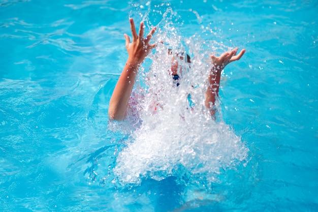 푸른 물이있는 야외 수영장에서 다이빙하는 동안 물을 뿌린 8 세 어린이의 손