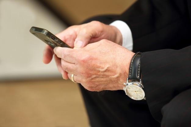 휴대 전화와 노인 비즈니스 남자의 손