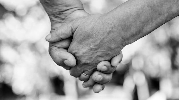 Руки пожилой пары, крупным планом. пожилая пара, держась за руки во время прогулки. концепция любви. концепция заботы зрелых вместе.