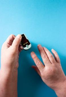 맥박 산소 측정기를 들고 노인 여성의 손에 맥박 산소 측정기로 산소 포화도를 측정합니다. 건강 개념.