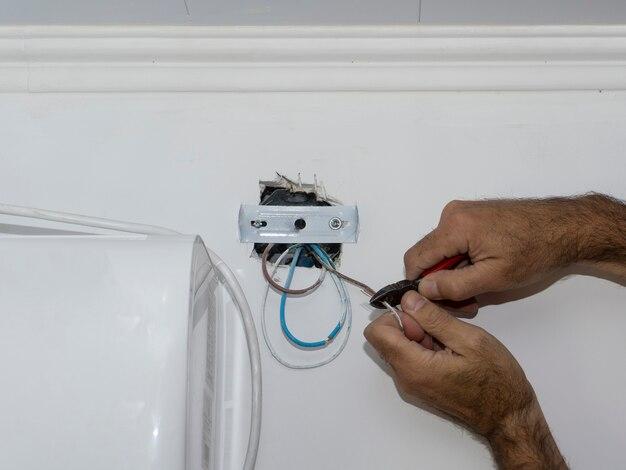 Руки электрика зачистки электрических кабелей для установки светильника