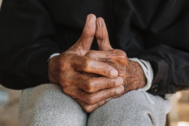 木のテーブルの上の老人の手。ヴィンテージトーン