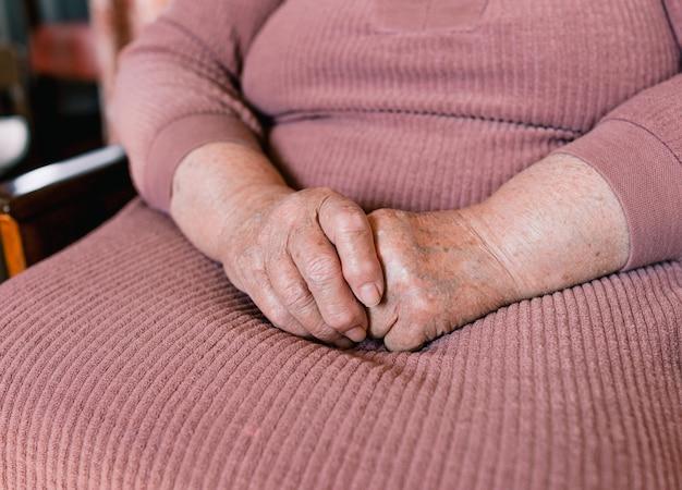 シワやシミのある老婆の手がクローズアップ。引退した女性