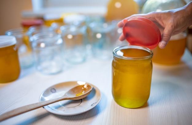 未知の女性の手は、大きな白い木製のテーブルの上に立って、木のスプーンで小さな受け皿の隣に、ゴム製の蓋付きの純粋な甘い金色の蜂蜜で透明なガラスの瓶を閉じます