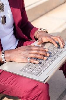 도시의 계단에 앉아 컴퓨터 작업을 하는 알아볼 수 없는 아프리카 남자의 손