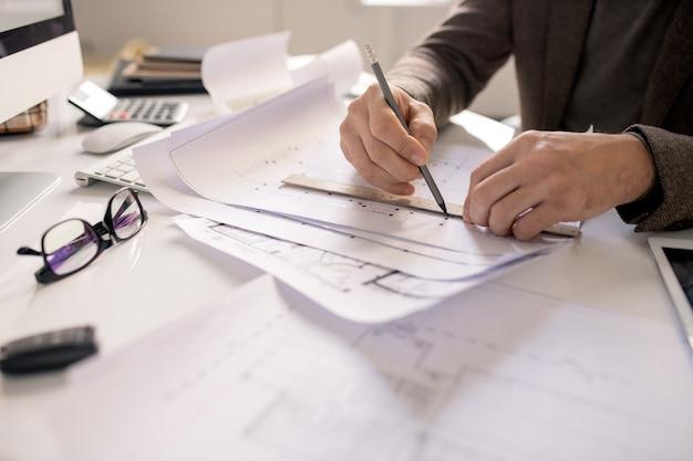 Руки архитектора с карандашом и линейкой, рисующей линию, работая над эскизом проекта нового здания на рабочем месте