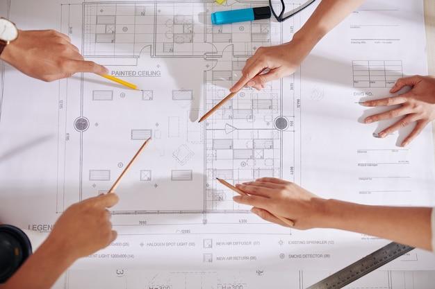 将来のインテリアデザインプロジェクトについて話し合うときに、テーブルの青写真を指し示す建築家やデザイナーの手