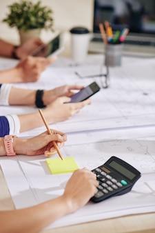 彼らが取り組んでいるプロジェクトのコストを数える建築家とインテリアデザイナーの手