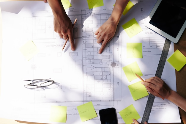 建築設計図を指している建築家やエンジニアの手、上からの眺め