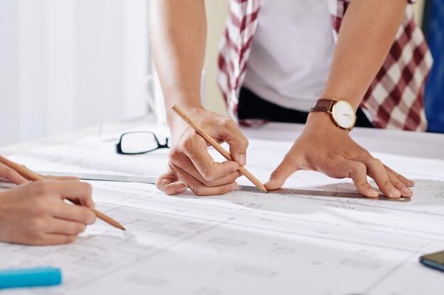 建築の建設計画に取り組んでいる建築家の手と鉛筆で詳細を描く