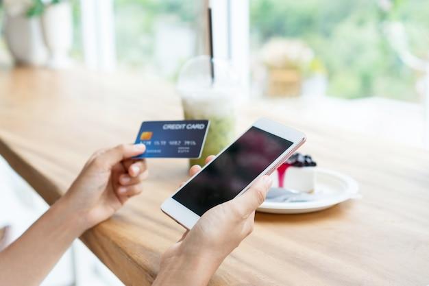 Руки азиатской женщины с помощью смарт-телефона, держа кредитную карту в кафе.