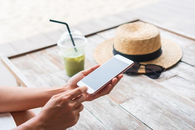 카페에서 나무 테이블에 아이스 말차 라떼, 모자, 선글라스와 함께 스마트 폰을 사용하는 아시아 여자의 손. 확대. 주말 개념에서 휴식을 취하십시오.