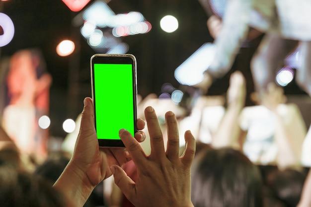 聴衆の手は、パーティーコンサートで緑色の画面でモバイルスマートフォンで写真を撮る人々を群衆します。