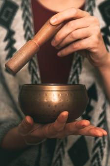 手作りのポンチョコピースペース瞑想垂直に身を包んだチベットのボウルを使用している女性の手