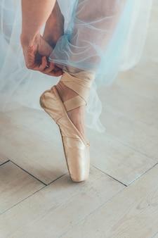 青いチュチュスカートのバレリーナの手は、白い光のホールで脚にトウシューズを履きます