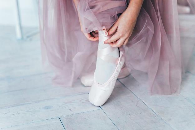 ピンクのチュチュスカートのバレリーナの手は、ダンスクラスの脚にトウシューズを履きます