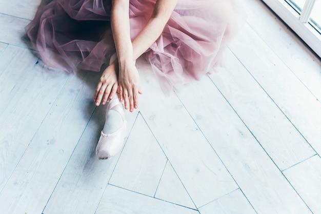 ピンクのチュチュスカートのバレリーナの手は、白い光のホールで脚にトウシューズを履きます。若いクラシックバレエダンサーの女の子