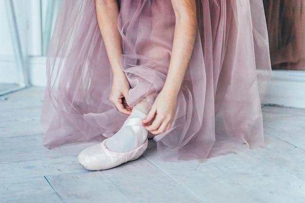 ピンクのチュチュスカートのバレリーナの手は、白い光のホールで脚にトウシューズを履きます