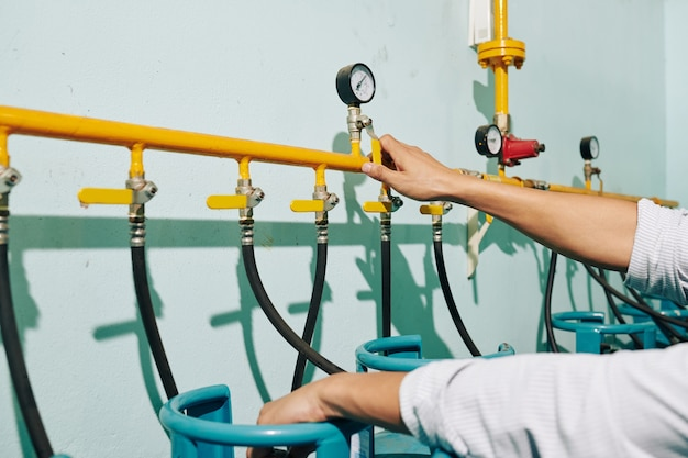 Руки бариста проверки давления в газовых трубах