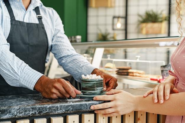 Руки бариста подают чашку горячего какао-напитка, украшенную маршмеллоу, на прилавке