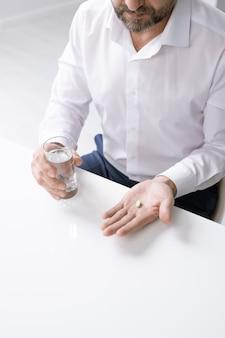 オフィスの机の上にピルと水のガラスを保持している頭痛とひげを生やしたビジネスマンの手