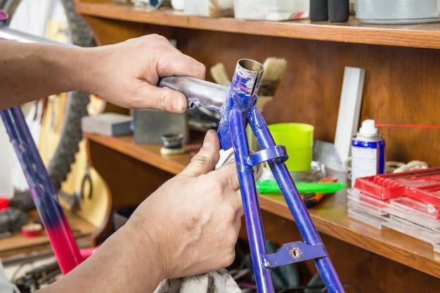 ワークショップで破損したフレームバイクを掃除する自転車整備士の手