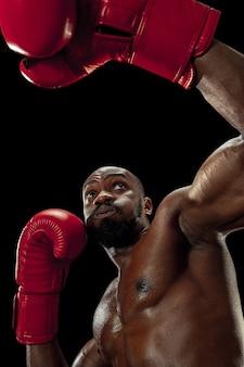 黒の背景にボクサーの手。強さ、攻撃と動きの概念。アフリカ系アメリカ人のモデルを動かしてください。スポーツユニフォームのアフロ筋肉アスリート。ボクシング中のスポーティな男