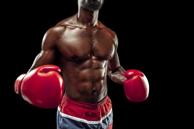 Руки боксера на черном фоне. концепция силы, атаки и движения. подходит афро-американская модель в движении. афро-мускулистый спортсмен в спортивной форме. спортивный мужчина во время бокса