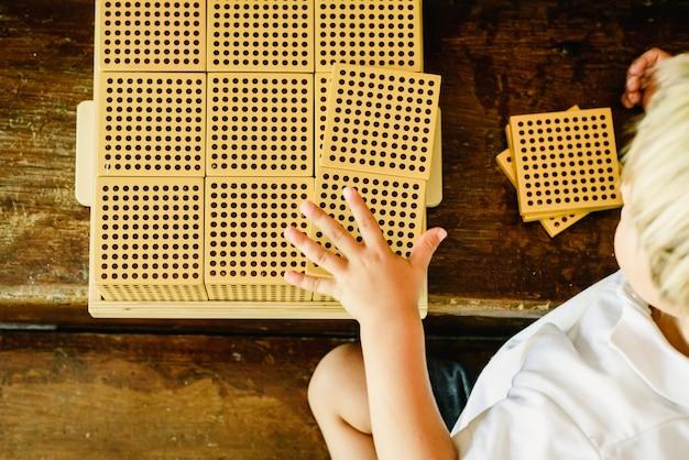 モンテッソーリの教室で木製の背景にカウントの立方体を操作する少年の手