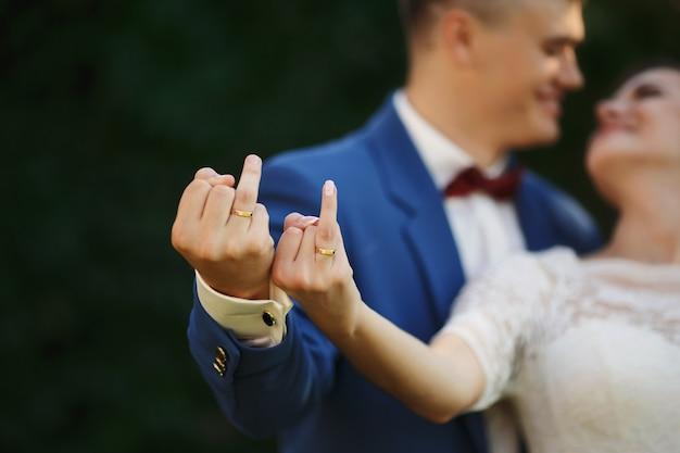 신부와 신랑의 결혼 반지에 손입니다. 부부는 장난스럽게 반지를 보여줍니다.