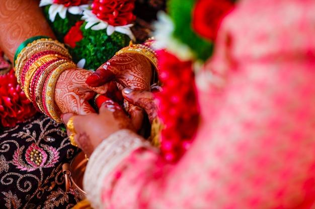 Руки невесты красиво украшены индийским искусством менди вместе с украшениями и красочными браслетами.