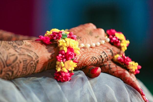 花嫁の手は、ジュエリーやカラフルな腕輪と一緒にインドの一時的な刺青アートで美しく装飾されています