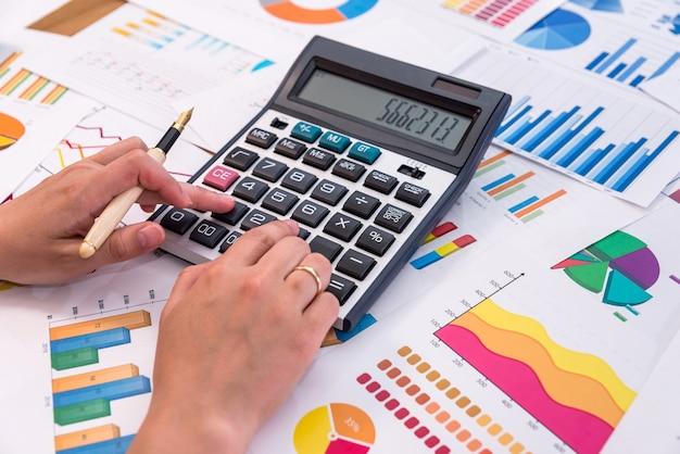 그래프와 다이어그램을 계산하는 비즈니스 분석가의 손