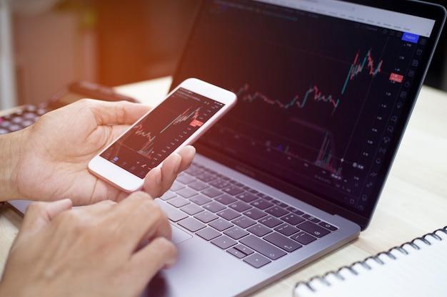 スマートフォンを持っているビジネスマンと分析を行う働く株式トレーダーの手