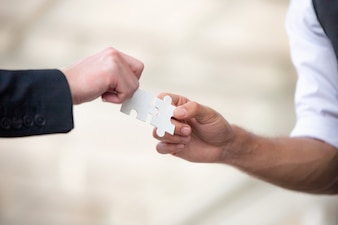 Hands of business people hold paper jigsaw puzzle together,Business team assembling Jigsaw