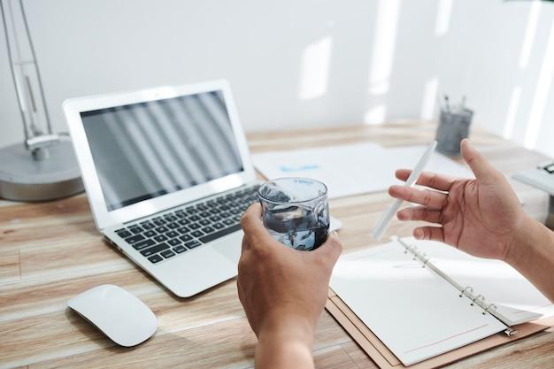 Руки делового человека пьют стакан воды и играют с ручкой после окончания работы над большим проектом