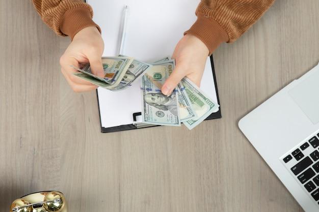 돈을 계산 하 고 사무실 책상에 메모하는 사업가의 손에.