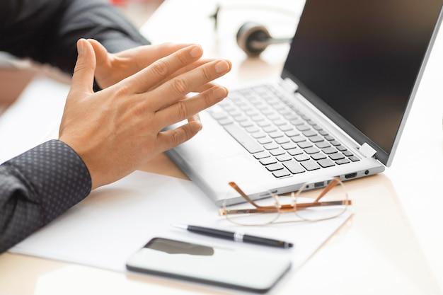 オンラインビデオ通話中のビジネスマンの手。ノートパソコンのモニターの前で人間。