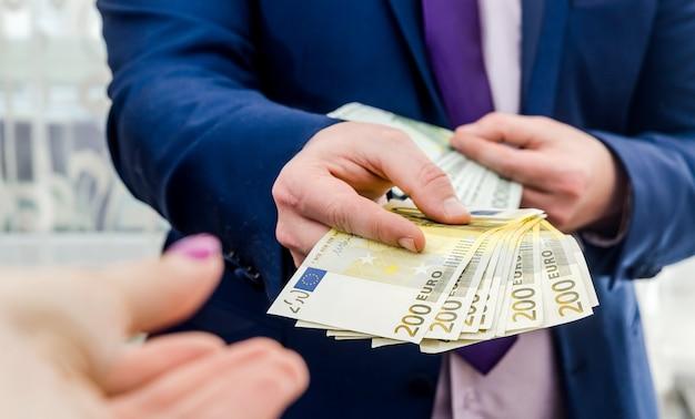 ユーロ紙幣を与えるビジネスマンの手。