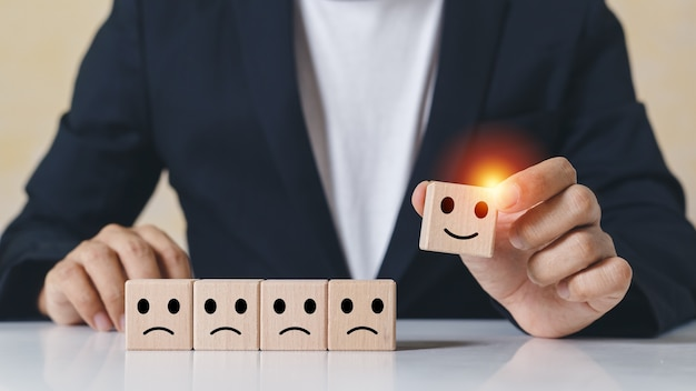 ビジネスマンの手は、笑顔の感情のアイコンと選択された不幸な感情ではなく、選択された木製の立方体のブロックを拾います。ビジネスコンセプトの評価とランク付け。