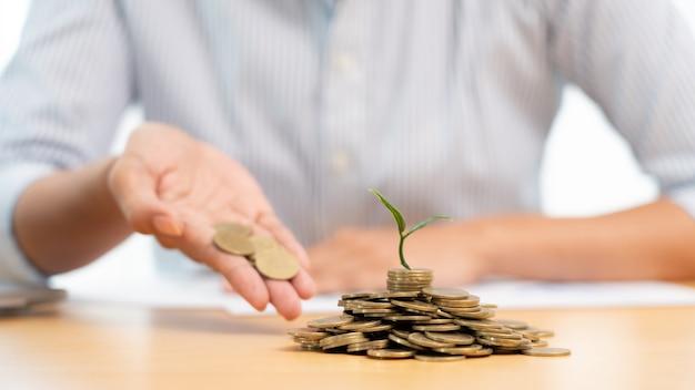 사업가의 손에 동전을 식물에 넣어 수익을 내며 성장하고 계획 및 투자 계획을 저장하여 재정적 성장을 보여줍니다.