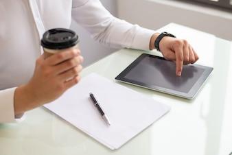 デジタルタブレットを使用してコーヒーを保持しているビジネスマンの手