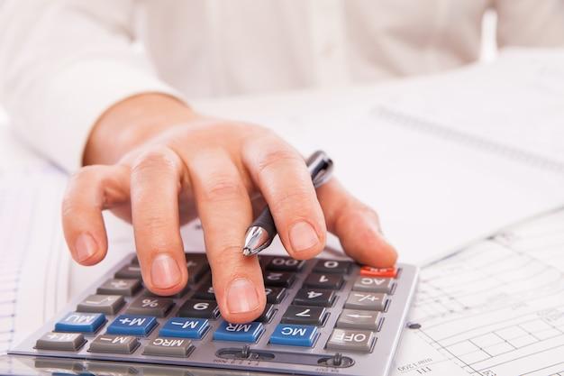電卓を持つビジネスマンの手。財務会計事業。