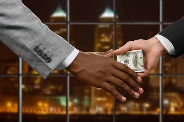 お金を渡すビジネスマンの手。手は夜に現金を渡します。すべてのチェーンには弱点があります。最高の状態での腐敗。