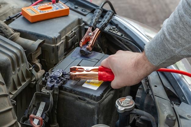 Руки автомеханика с помощью перемычки автомобильного аккумулятора для запуска двигателя