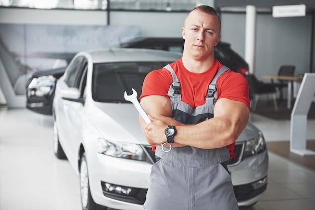 ガレージでレンチで自動車修理工の手。