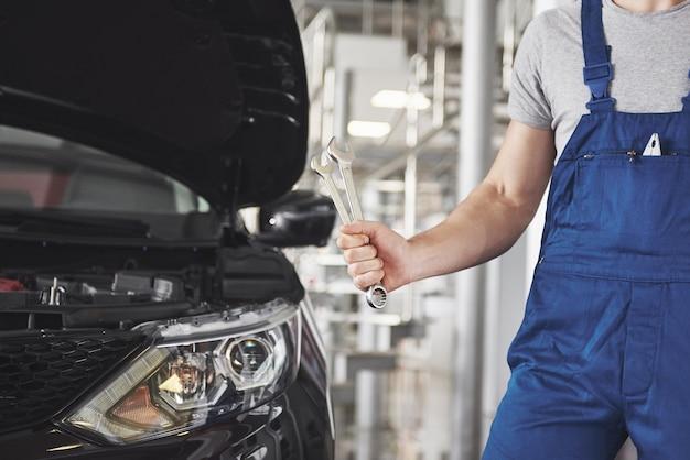 Руки автомеханика с гаечным ключом в гараже.
